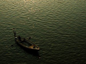 Lonely fisher man in traditional Indian fishing boat